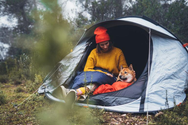 Frau mit Hund beim Camping
