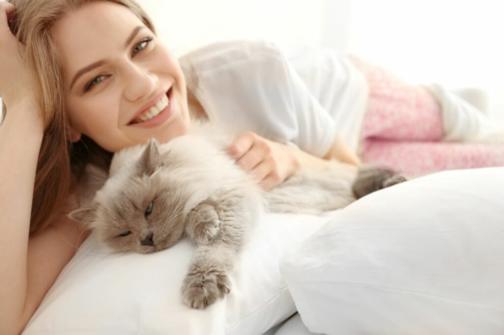 Katzensitter liegt mit Katze auf dem Sofa.